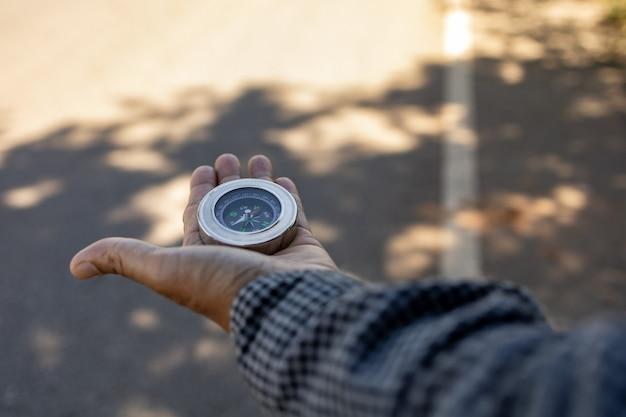 Männlicher reisender, der einen magnetkompass auf asphaltstraße hält, orientierung und den weg findet.