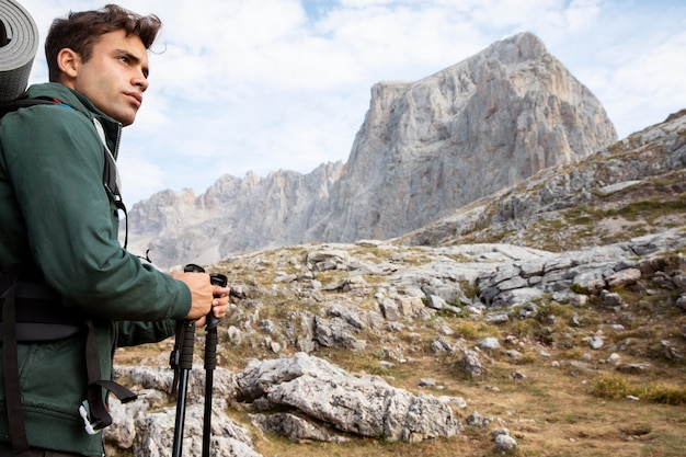 Männlicher reisender, der in den bergen wandert, während er seine wichtigsten sachen im rucksack dabei hat