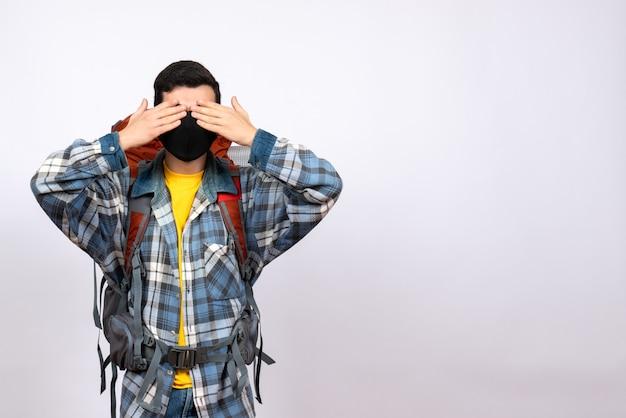 Männlicher reisender der vorderansicht mit rucksack und maske, die augen mit händen bedeckt