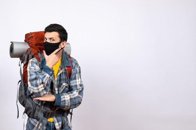 Männlicher reisender der vorderansicht mit rucksack und maske, die hand auf sein kinn setzen
