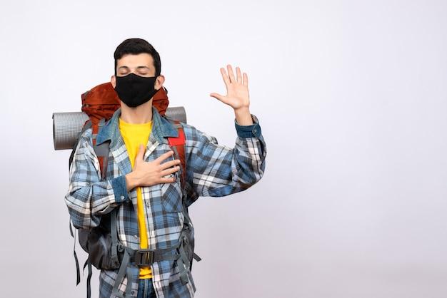 Männlicher reisender der vorderansicht mit rucksack und maske, die mit handgeste versprechend sind