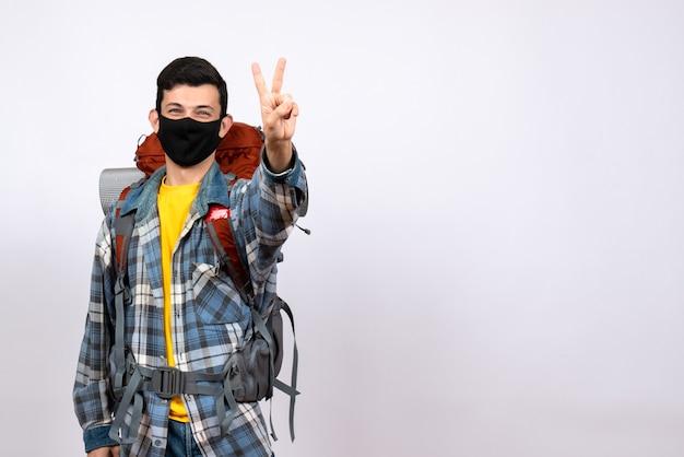 Männlicher reisender der vorderansicht mit rucksack und maske, die siegeszeichen machen