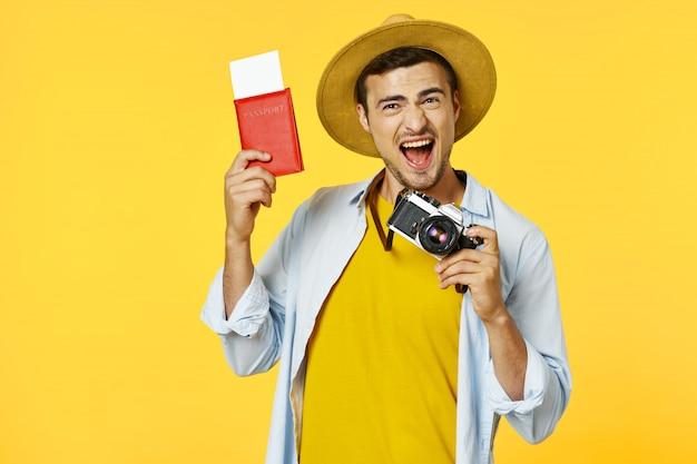 Männlicher reisender mit einem koffer, farbiger oberfläche, freude, reisepass