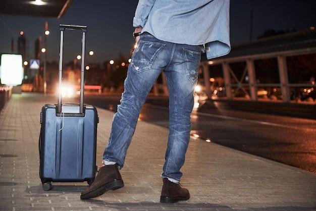 Männlicher reisender mit einer gepäcktasche, der in der nacht steht und nach dem auto ruft