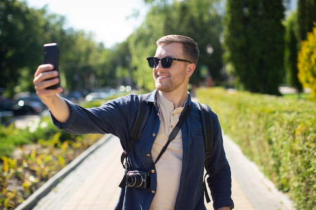 Männlicher reisender mit einer kamera in einem örtlichen park
