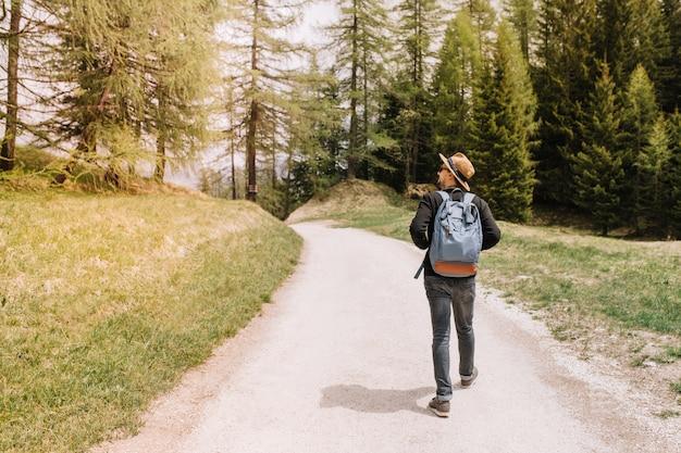 Männlicher reisender mit großem blauen rucksack, der zum walddickicht geht und sich mit interesse umschaut