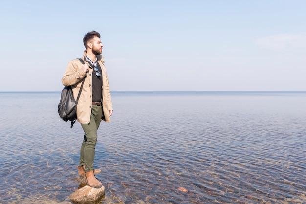 Männlicher reisender mit seinem rucksack, der idyllischen ruhigen see betrachtet