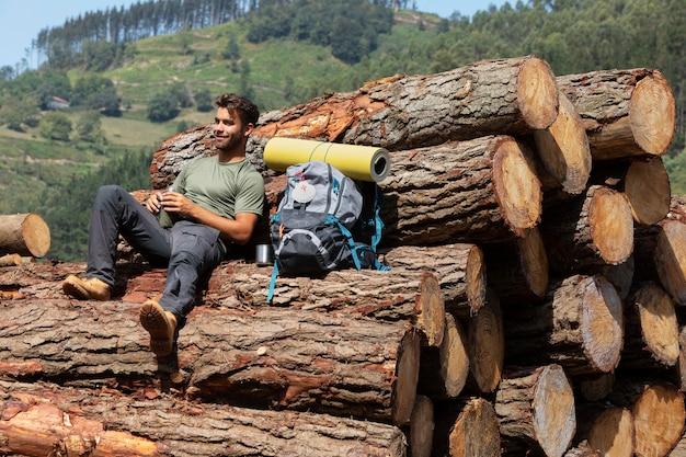 Männlicher reisender sitzt auf einem haufen holzstämme