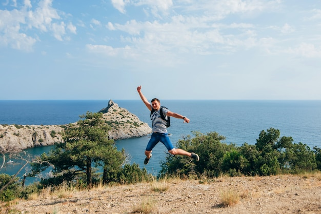 Männlicher reisender springt fröhlich und glücklich in die natur