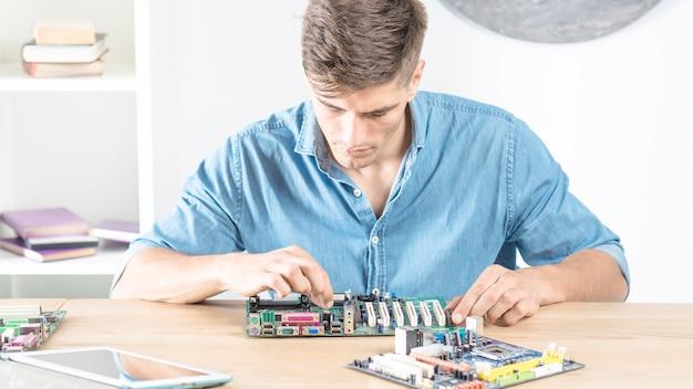 Männlicher reparatur it-techniker, der das motherboard aufrüstet