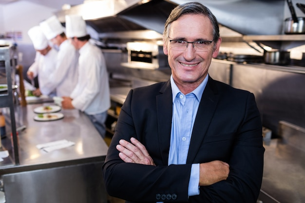 Männlicher restaurantmanager, der mit den armen gekreuzt steht