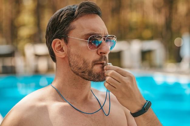 Männlicher rettungsschwimmer mit sonnenbrille in der nähe des öffentlichen schwimmbads