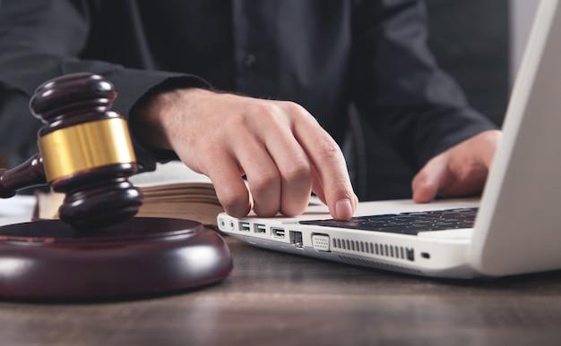 Männlicher richter, der in der laptoptastatur tippt. gerechtigkeit und recht
