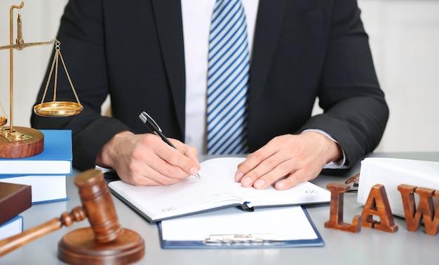 Männlicher richter, der mit dokumenten- und gesetzeszubehör auf dem tisch arbeitet