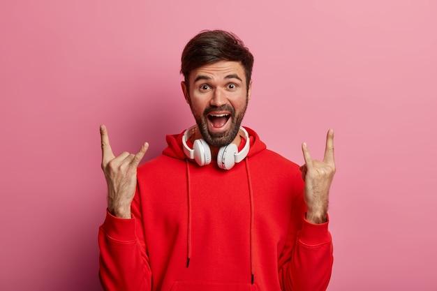 Männlicher rocker genießt positive stimmung, hört rock'n'roll, coole musik im club, verwendet moderne stereokopfhörer, trägt einen roten hoodie, posiert an einer rosigen pastellwand und zeigt eine horngeste. körpersprache