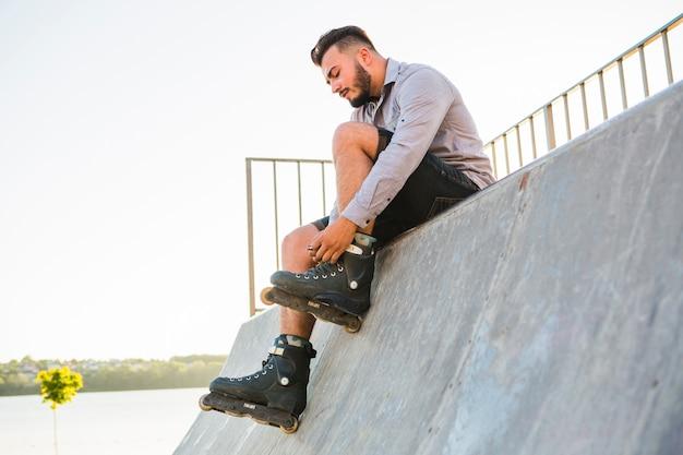 Männlicher rollerskater, der auf rollerskate im rochenpark sich setzt