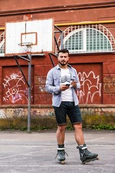 Männlicher rollerskater unter verwendung des handys im basketballplatz