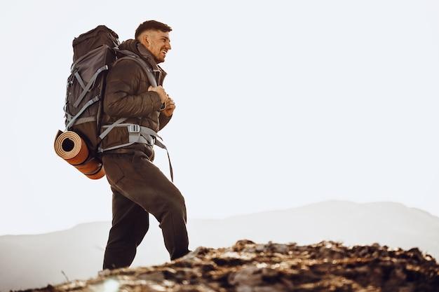 Männlicher rucksacktourist in der wanderausrüstung, die an der spitze des berges steht