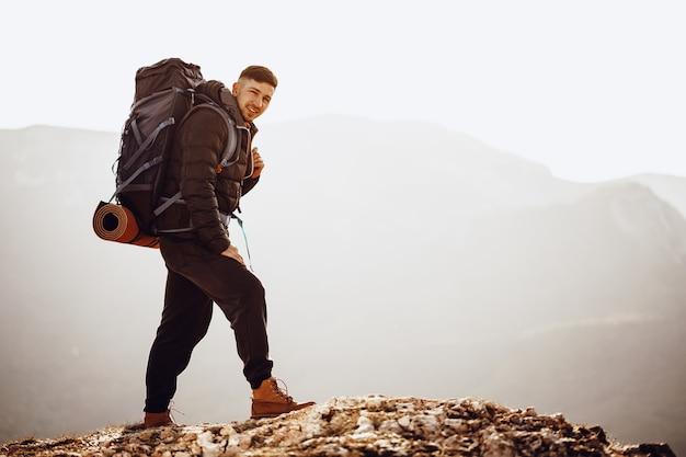 Männlicher rucksacktourist oder wanderer in wanderausrüstung, die oben auf dem berg steht