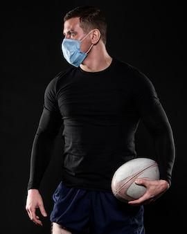 Männlicher rugbyspieler mit medizinischer maske und ball