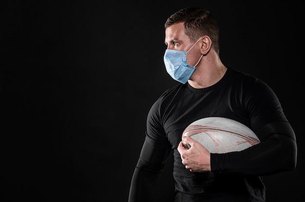 Männlicher rugbyspieler mit medizinischer maske und kopienraum
