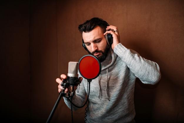 Männlicher sänger, der ein lied im musikstudio aufzeichnet. sänger in kopfhörern gegen mikrofon.