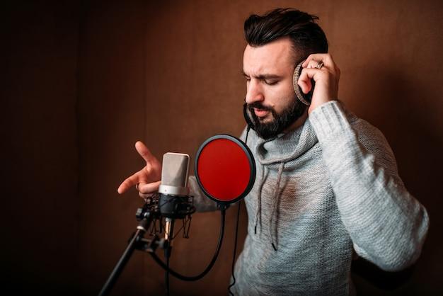 Männlicher sänger, der ein lied im musikstudio aufzeichnet
