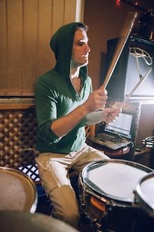 Männlicher schlagzeuger, der schlagzeug im tonstudio spielt