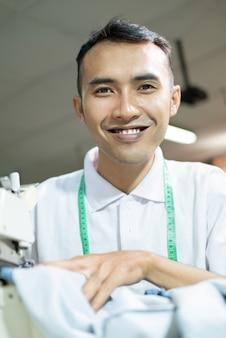 Männlicher schneider lächelt beim nähen mit einer nähmaschine