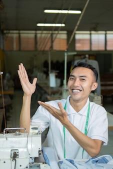 Männlicher schneider lächelt mit einer aufwärtsbewegung seiner hand, um beim nähen mit der nähmaschine etwas zu präsentieren