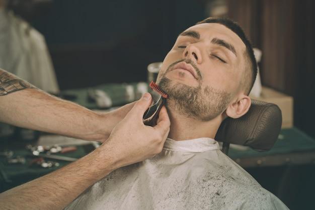 Männlicher schönheitstag. geerntete nahaufnahme eines jungen mannes, der seinen bart in einen friseursalon formen lässt