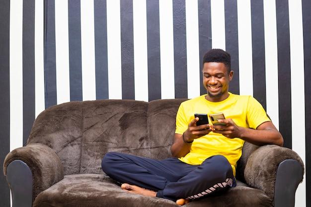 Männlicher schwarzafrikanischer hipster, der das datum drahtlos von einem telefon auf ein anderes überträgt
