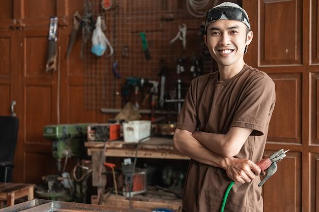 Männlicher schweißer lächelt mit gekreuzten händen, während er elektrischen schweißer im hintergrund der schweißwerkstatt hält