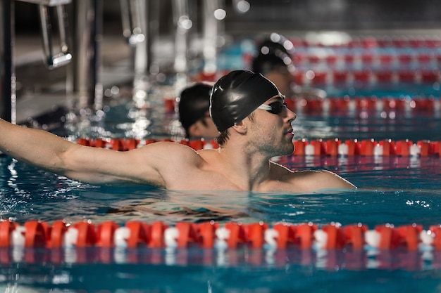 Männlicher schwimmer, der den rand eines schwimmbades hält