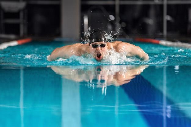 Männlicher schwimmer, der den schmetterlingsschlag schwimmt