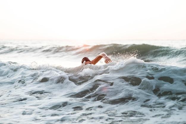 Männlicher schwimmer, der im ozean schwimmt
