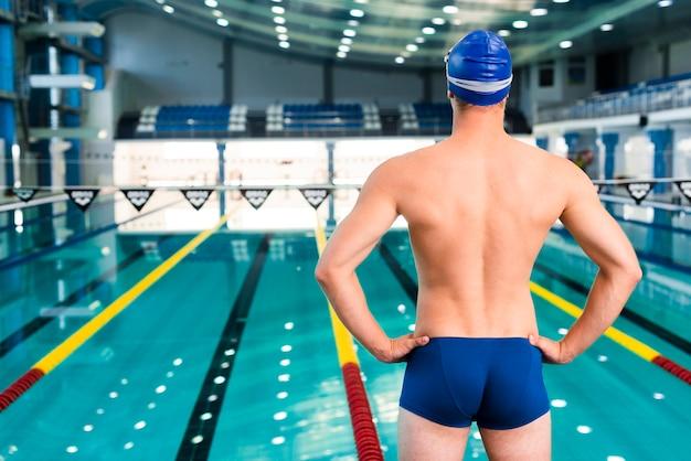 Männlicher schwimmer, der pool betrachtet
