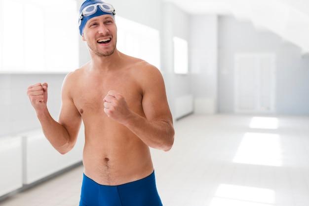 Männlicher schwimmer, der sieg feiert