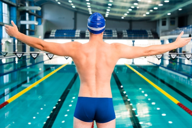 Männlicher schwimmer, der vor dem schwimmen aufwärmt