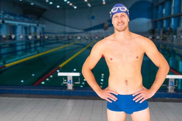 Männlicher schwimmer, der vor swimmingpool aufwirft
