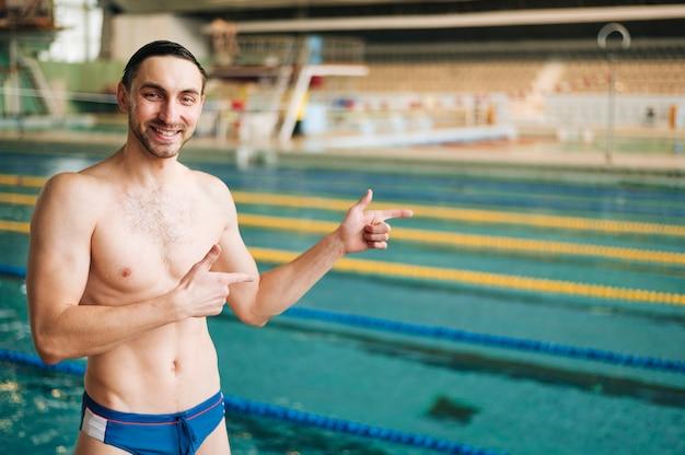 Männlicher schwimmer der vorderansicht, der auf becken zeigt