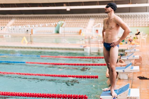 Männlicher schwimmer des hohen winkels, der auf poolrand steht