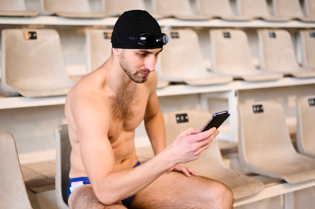 Männlicher schwimmer des hohen winkels in der pause unter verwendung des mobiles