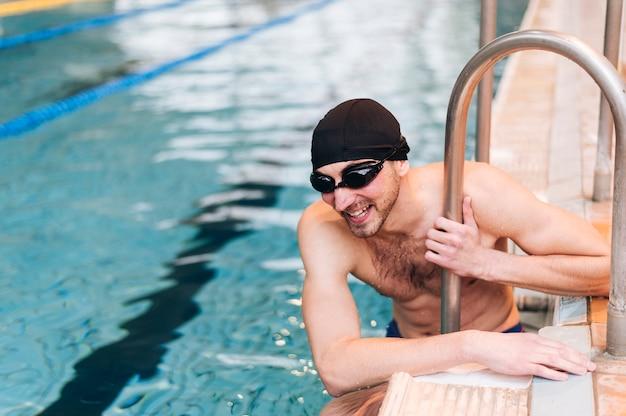 Männlicher schwimmer des hohen winkels in der pause