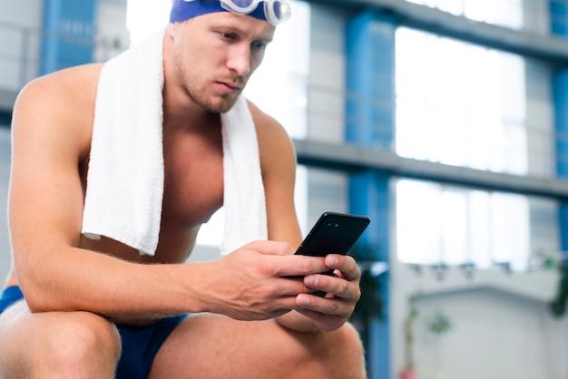 Männlicher schwimmer des niedrigen winkels, der mobile überprüft