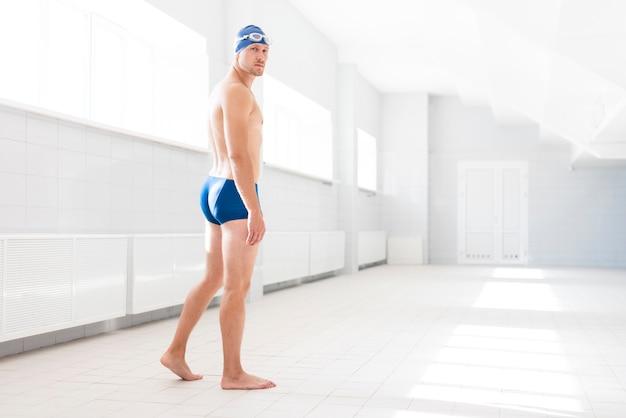 Männlicher schwimmer des niedrigen winkels, der nach schaut