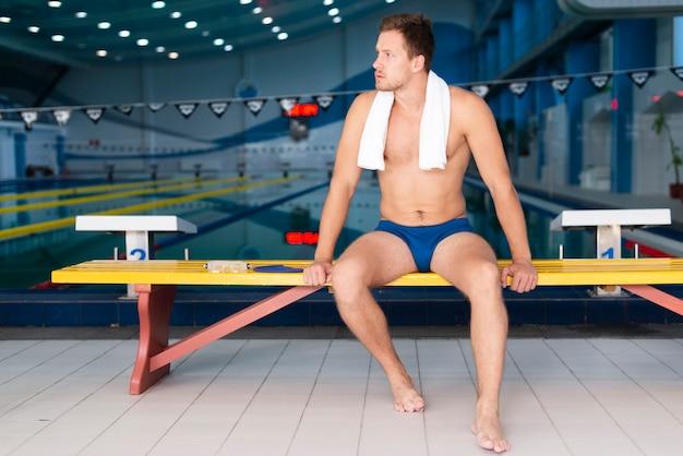 Männlicher schwimmer des niedrigen winkels, der pause hat