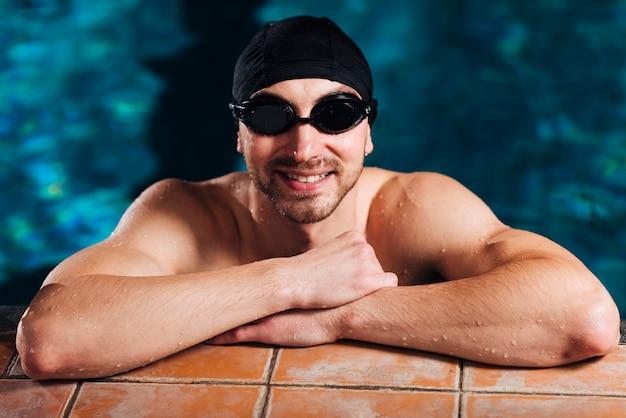 Männlicher schwimmer des smiley, der auf bassinrand sich lehnt