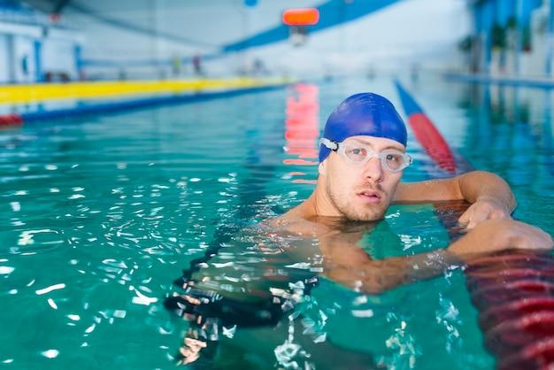 Männlicher schwimmer im wasser, das fotografen betrachtet
