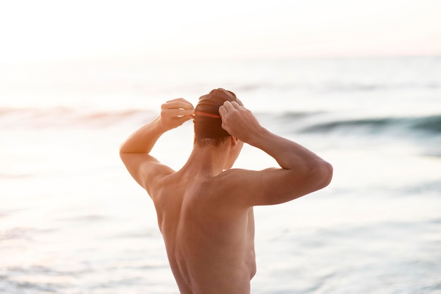 Männlicher schwimmer mit schutzbrille und mütze
